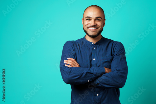 Fotografía Portrait of a dark-skinned cheerful smiling man against turquoise background