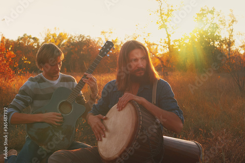 Fotografía Two hippie men playing djembe drum and acoustic guitar in the autumn in the forest at sunset