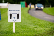 A Covid-19 Social Distancing Sign Staked Into Grass Next To A Road At An Outdoor Event