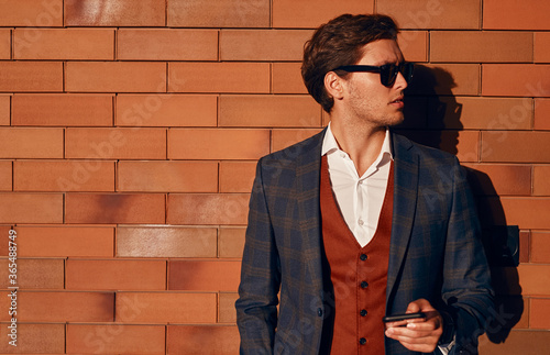 Confident businessman with smartphone standing near brick wall Canvas Print