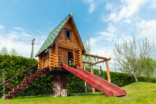 Canvas Small wood log playhouse hut with stairs ladder and wooden slide on children playground at park or house yard