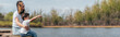 Leinwanddruck Bild - panoramic concept of cute kid pointing with finger while sitting near happy mother and lake