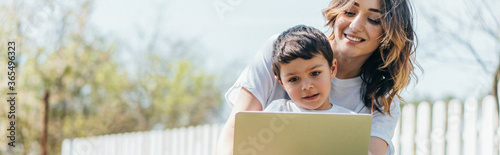 Fotografiet horizontal concept of happy mother and son using laptop outside