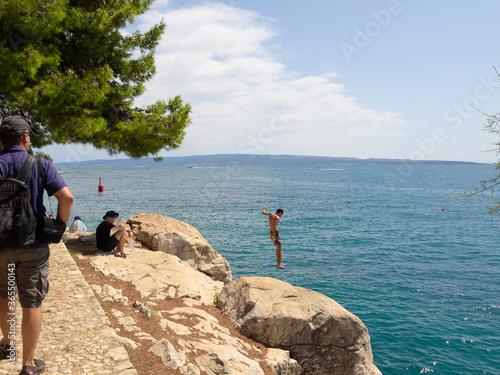 Fototapeta Turistas saltando de las rocas en la costa de Split, Croacia, verano de 2019