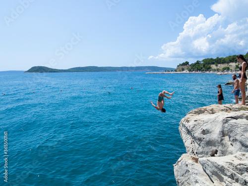 Obraz na plátně Turistas saltando de las rocas en la costa de Split, Croacia, verano de 2019