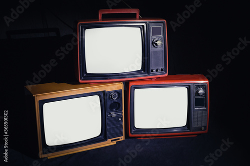 Photo Three old antique TV with white screen in a dark room, classic, vintage, television on a black background
