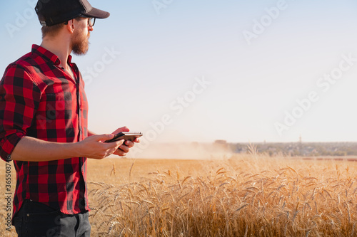Millennial man with a tablet in a dusty agricultural field Canvas Print