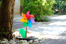Wind Turbine Toy In Sunflower Shape, Decorated By Planting In Flowerpot Buried In The Ground Under A Big Tree