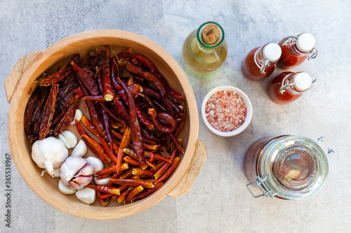 Fotografie, Obraz Wooden bowl with dried hot chili peppers and garlic cloves