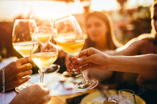 People clinking glasses with wine on the summer terrace of cafe or restaurant - fototapety na wymiar