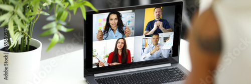 Fototapeta Woman talking with international colleagues using online video chat service at workplace obraz