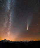 Night landscape of mountains with stars covered Milky Way sky and Neowise comet with light tail.