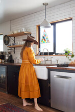 Woman In Cowboy Hat And Yellow Dress Washing Herbs In A Country Kitchen, Copyright Diana Koenigsberg 2020