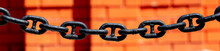 A Large Metal Chain Near A Red Brick Wall.