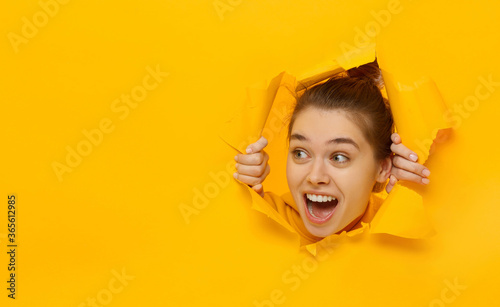 Fotomural Excited girl looking through hole in paper at left with eyes round with surprise