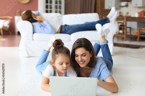 Happy mom and little child girl looking at screen laptop, talking to webcam, chatting online via computer app.