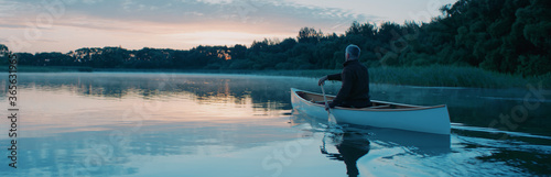 Man canoeing in a traditional wooden boat on a large lake at dawn Fotobehang
