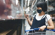 Asian Pregnant Woman in face mask using smartphone while shopping