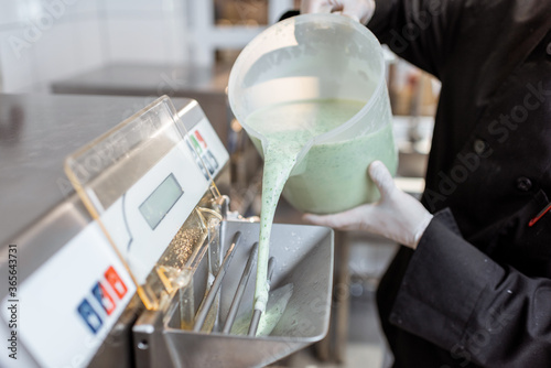 Chef pouring mixed milk base into the ice cream machine or freezer, close-up