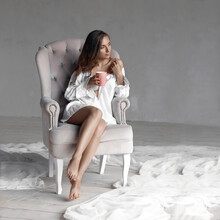 Sedctive Beautiful Closeup Portrait Of Sexual Tanned Girl With Long Curly Hair In White Men's Shirt Sitting In Pink Luxury Armchair With Cup Of Hot Coffee.