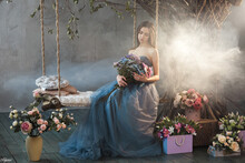 Artistic Beautiful Woman In Long Blue Dress Sitting On The Swing Near The Tree With Fog. Womanl Is Surrounded By Many Flowers. Artistic Fantasy Beautiful Banner For Advertisments.