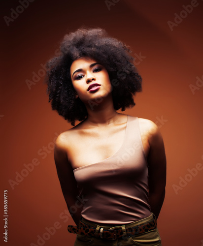 Valokuva pretty young african american woman with curly hair posing cheerful gesturing on