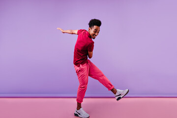 Full-length shot of trendy african male model in pink clothes. Excited black man in stylish sneakers dancing on purple background.