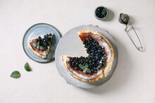 Homemade Blueberry Baked Soft Cheesecake San Sebastian, Whole And Sliced, On Ceramic Plate Decorated By Fresh Wild Berries, Icing Sugar And Mint Over White Texture Background. Flat Lay, Space