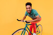 Active african guy in green t-shirt sitting on bike. Laughing black young man posing with bicycle on bright background.