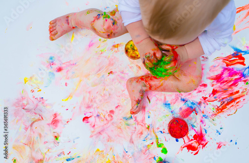 Top view Happy cheerful dirty baby playing with paint on white background Fototapet