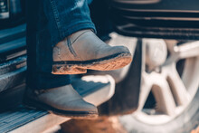 Girl Sits In Car With Her Legs Dangling In Jeans And Hiking Boots After Hike.