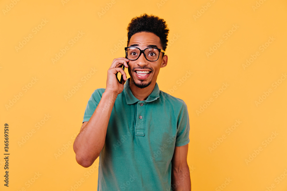 Fototapeta Funny curly guy talking on phone with surprised smile. Indoor photo of amazed black man isolated on yellow background with smartphone.