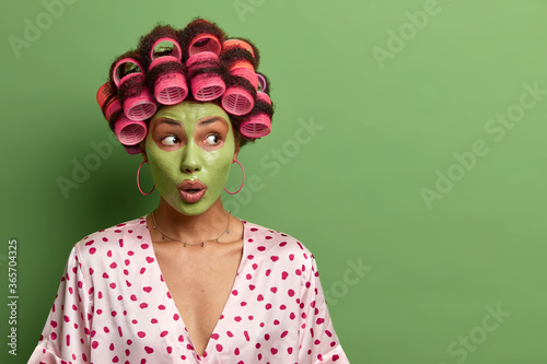 Studio shot of impressed shocked woman applies fresh clay mask for healthy skin, does beauty procedure and facial treatments, wears hair curlers and domestic robe, blank space on green wall Wallpaper Mural