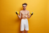 Photo of skinny man goes in for sports, builds muscles at home, has effective training complex with dumbbells, wears white shorts, poses with naked torso against yellow background. Health care concept