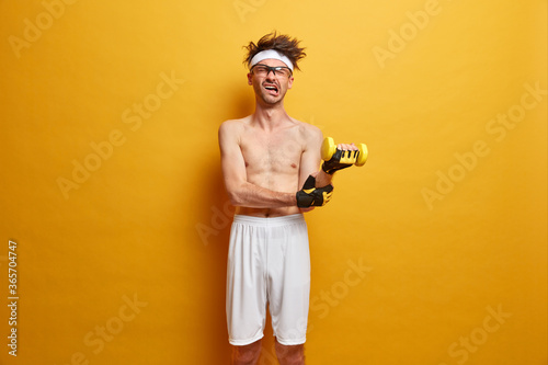Fitness sporty guy raises heavy dumbbell, does exercise for arms, has much energy, feels pain, shows sport motivation, wears shorts and sport gloves. People, health, body care and home fitness concept