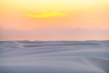 White sands national park monument sand dunes in New Mexico with Organ mountains silhouette on horizon during colorful red yellow sunset - 365714505