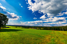 Open Rural Scenery With A Big Grassland Area On A Sunny And Cloudy Day With Light Beams