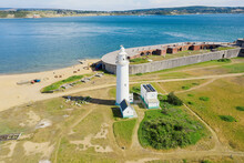 Aerial View Of Hurst Point, In The United Kingdom. Lighthouse By The Sea With The Castle In The Background By The Sea.