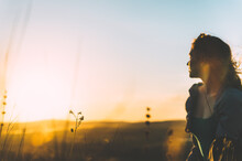 Blurred Figure Of A Young Woman Watching The Sunset