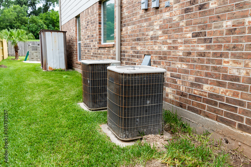 Two older HVAC air conditioner systems next to brick home with copy space Canvas Print
