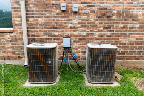 Older HVAC air conditioner units next to brick home with copy space Canvas Print