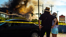 Silhouette From Behind Of Mother And Daughter Watching Hopelessly At Their Home Burning In Flames. Firefighters Trying To Put Out A Fire At A Residential Building. A Risky Job Only For The Brave.