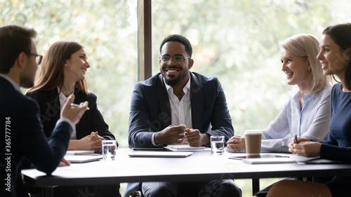 Five positive multi ethnic company staff gather together sit at boardroom desk talking planning future project Billede på lærred