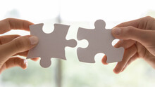 Close Up View Two Female Hands Holding Pieces Join Puzzles Having Fun Play Game. Connecting Jigsaw, Finding Best Match Right Solution, Help In Business, Bond And Mental Connection, Brain Work Concept