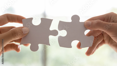 Fototapeta Close up view two female hands holding pieces join puzzles having fun play game. Connecting jigsaw, finding best match right solution, help in business, bond and mental connection, brain work concept obraz