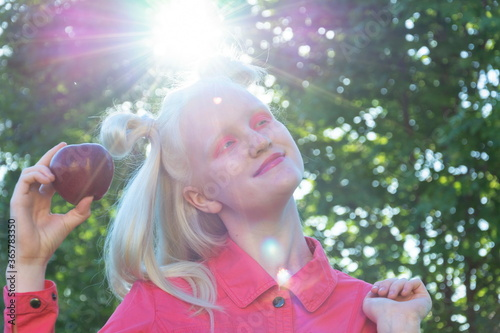 Valokuva An albino girl in a red blouse against a background of green leaves and sunlight
