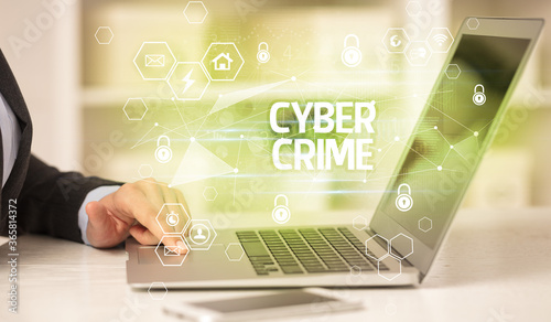 Photo CYBER CRIME inscription on laptop, internet security and data protection concept