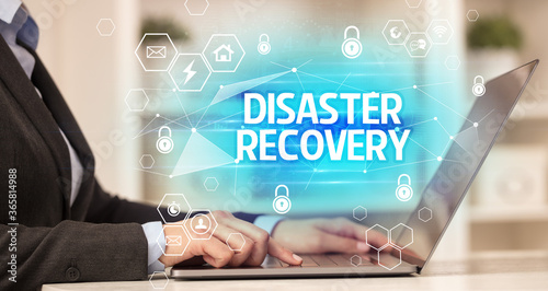 Fototapety, obrazy: DISASTER RECOVERY inscription on laptop, internet security and data protection concept, blockchain and cybersecurity
