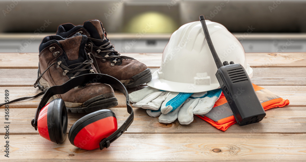 Fototapeta Work safety protection equipment. Industrial protective gear on wooden table, blur construction site background.