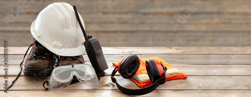 Fototapeta Work safety protection equipment. Industrial protective gear on wooden table, blur construction site background. obraz